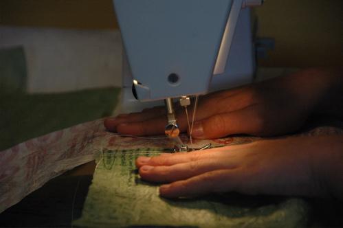 Eli guides fabric in the machine