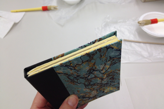 lining up the text block inside the book case before gluing the end papers inside